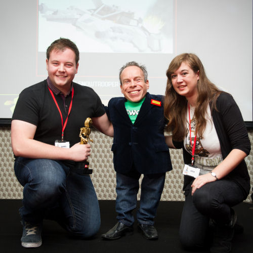 Daniel Jameson, with partner, receiving his Golden Brickie award from Warwick Davis