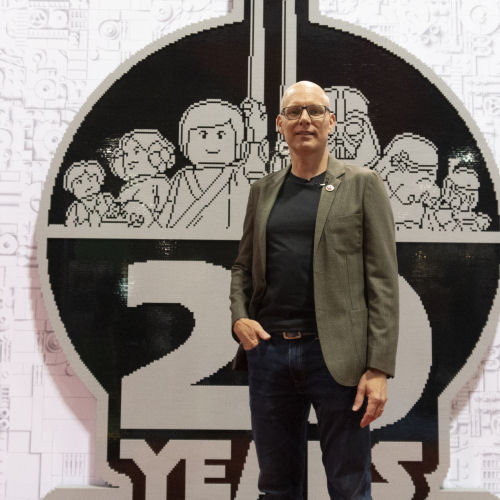 Michael Lee Stockwell in front of brick-built LEGO Star Wars logo